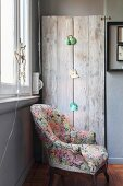 Floral armchair in front of retro reading lamps mounted on rustic wooden boards