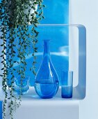 Rounded carafe and blue drinking glasses on metal shelf below trailing succulent