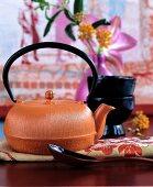 Orangefarbene Teekanne aus Gusseisen mit Deko in Rottönen