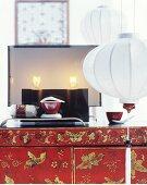 Moderne Tischleuchte auf einem Lackschränkchen, weiße Lampions