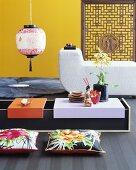 Niedriger Asia-Tisch mit Bodenkissen vor Polstermöbel und gelber Wand