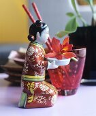 Small figurine of kneeling Chinese woman holding orchid flower