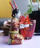 Kleine kniende, chinesische Figur trägt eine Orchideenblüte