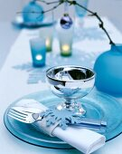 Festive place setting with ice-blue glass plates, shiny goblet and felt napkin ring