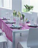 Festlich gedeckter Tisch mit weißen Hyazinthen, Menükarten und mauvefarbenen Tischläufern