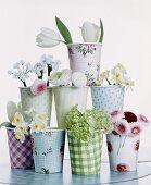 Verschiedene Pappbecher mit unterschiedlichen Frühlingsblüten dekoriert und gestapelt
