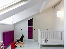 Attic nursery with fitted wardrobes under sloping ceiling