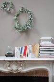 Two wreaths of dried leaves above books on mantelpiece of open fireplace