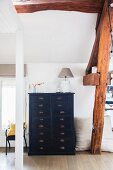 Black chest of drawers below rustic wooden beams