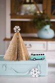 Christmas tree made from pages of old book and toy VW bus on old suitcase