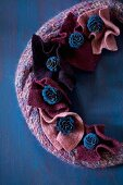 Knitted wreath decorated with pieces of felt and blue-painted larch cones