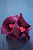 Small wooden hearts in squares of felt on blue surface