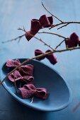 Schleifen aus Filz an einem Zweig und in einer blauen Schale