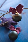 Black Christmas-tree bauble with felt ribbon on bare branch