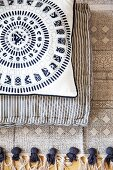 Two cushions with different patterns on ethnic fringed rug