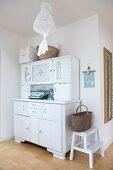 Basket on step stool next to white, vintage dresser