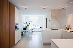 White floor and dining table in large, open-plan kitchen