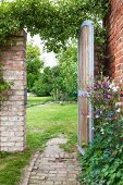 View of lawn seen through garden gate in brick wall