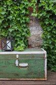 Alte Kiste und Laterne vor einer mit Efeu bewachsenen Wand