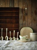 Sauce boat and silver spoons on white tablecloth against wooden wall