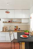 Kleine Küche mit hohen Oberschränken und Essplatz