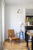 Designersessel aus Holz neben blauem Hocker und offenem Kamin