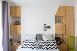 Bedroom flanked by fitted plywood cupboards