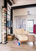 Chaise longue, stacked suitcases and vertical bookcase in reading corner