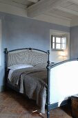Double bed against blue-grey wall below white-painted wood-beamed ceiling