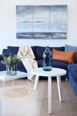 White side tables and dark blue couch below seascape painting on white wooden wall