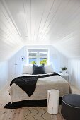 Double bed with pale and dark blankets below window in attic room with white wood-clad walls