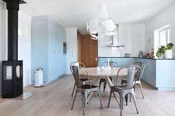 Grey retro metal chair and round classic table in dining area of blue-grey country-house kitchen