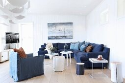 Maritime lounge area with white wood-clad walls, dark blue corner sofa, white side tables and TV