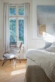 Wicker chair below window with linen curtains and bed in bedroom