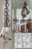 Spice rack with porcelain scoops, vintage-style storage jars and stuffed animals hung from butchers' hooks