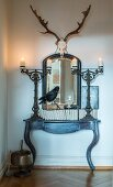 Lit candles in massive metal candlesticks on antique console table below mirror and hunting trophy