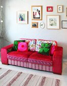 Romantic mixture of patterns on red sofa below framed pictures on wall