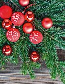 Red Christmas-tree baubles with hand-painted motifs on fir branch