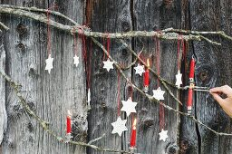 DIY modelling compound stars and red Christmas-tree candles on branch on board wall