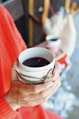 China beaker of mulled wine wrapped in fabric cover and held in hands