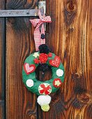Hand-crafted Christmas wreath with love-heart motifs hung on wooden door