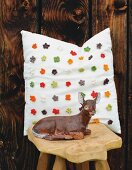 Retro deer figurine on wooden stool in front of cushion with appliqué crocheted flowers