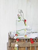 Garland of crocheted flowers draped around vintage glass bottle on rustic wooden crate