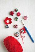 Bestickte Knöpfe, umhäkelt mit Blütenmotiven; Häkelnadel und roter Wollknäuel