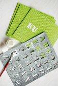Hellgrüne Schwammtücher mit Schablone und weißer Acrylfarbe beschriftet