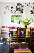 Colourful, geometric tablecloth on dining table, retro wooden chairs and collage of photos on wall above window