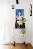 Collection of bottles and storage boxes on vintage serving trolley below portrait of woman on wall