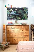 Turned candlestick on wooden stool in front of chest of drawers below picture of dinosaurs