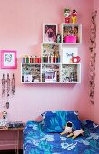 Blue bed linen on single bed and white modular shelving in child's bedroom with pink walls
