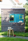 Saucepan on rustic wooden stool in front of wooden playhouse